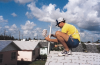 FSEC assistant John Broughton installs sensors on the roof of one of the monitored homes.